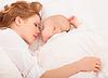 Madre abraza al bebé recién nacido durmiendo juntos en | Foto de stock