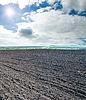 Czarny zaoranym polu pod błękitne niebo pochmurnie | Stock Foto