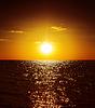 Złoty zachód słońca nad ciemną wodą | Stock Foto