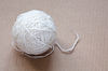 Ball of white wool yarn on cardboard background | Stock Foto