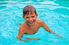 Uśmiechnięty chłopiec pływa w basenie na letnie wakacje | Stock Foto