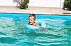 Przedszkole chłopak pływa w basenie na letnie wakacje | Stock Foto