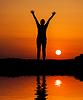 对橙色夕阳剪影的女人跳 | 免版税照片