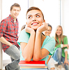Feliz estudiante sonriente con los libros en la escuela | Foto de stock