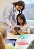 与老师和平板电脑在学校的小女孩 | 免版税照片