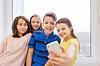 一批学校的孩子们服用自拍与智能手机 | 免版税照片