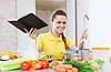 Szczęśliwa kobieta gotowania warzyw z książki | Stock Foto