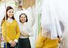 Shop assistant helps bride in choosing bridal veil | Stock Foto