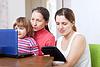 Glückliche Familie sieht elektronischen Geräten | Stock Photo