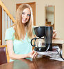Cute young blond with new coffee maker at table | Stock Foto