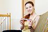 Lächelnde junge Frau mit Schwangerschaftstest | Stock Photo