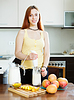 Cheerful woman making milk shake with mango | Stock Foto