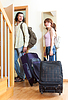 Couple with suitcases near door at home | Stock Foto