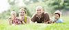 Czteroosobowa rodzina na zielonej trawie | Stock Foto