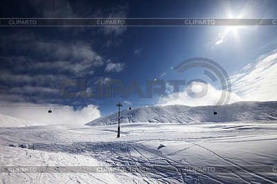 Ski slope, gondola lift and blue sky with sun | Foto stockowe wysokiej rozdzielczości |ID 3867995