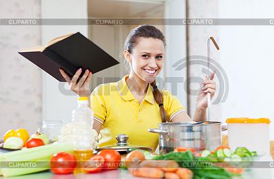 Szczęśliwa kobieta gotowania warzyw z książki | Foto stockowe wysokiej rozdzielczości |ID 3985368
