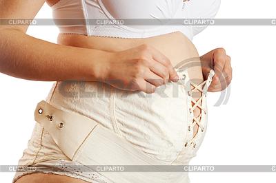 Kobieta w ciąży dressing pas macierzyńskiego | Foto stockowe wysokiej rozdzielczości |ID 4008936